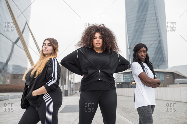 Three sportive young women posing in the city