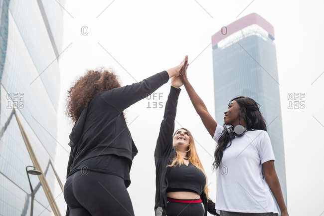 Three sportive young women high fiving in the city