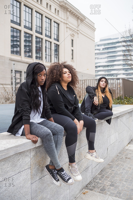 Three sportive young women sitting on a wall in the city