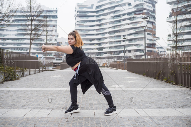Plus size sportive young woman training in the city