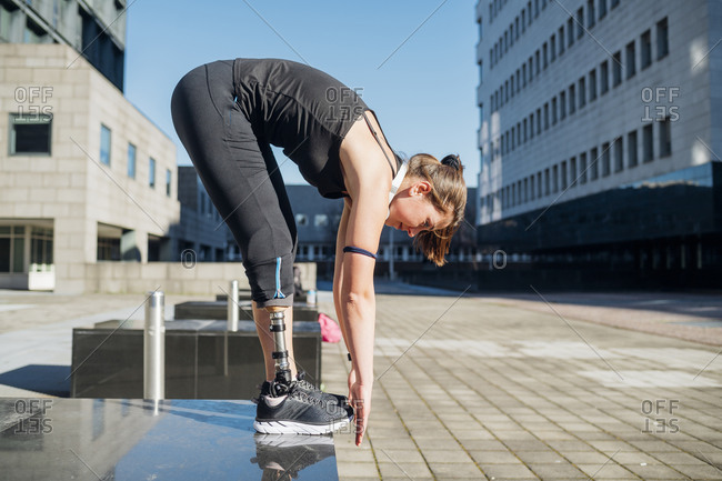 Sporty young woman with leg prosthesis practicing in the city