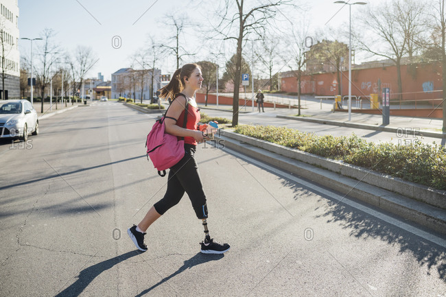 Sporty young woman with leg prosthesis walking in the city