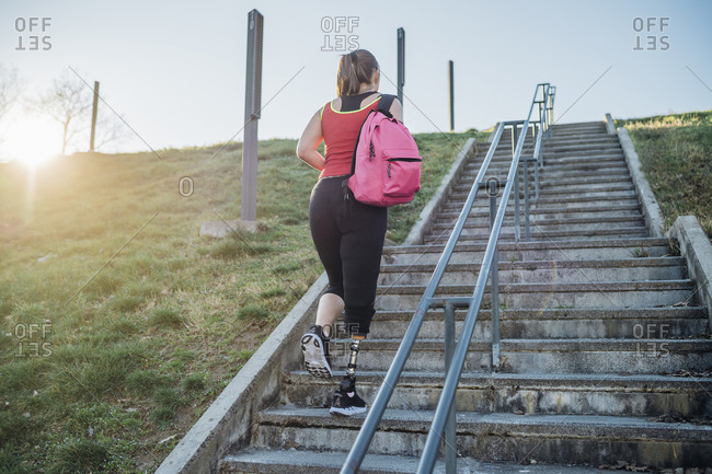 Sporty young woman with leg prosthesis walking up stairs