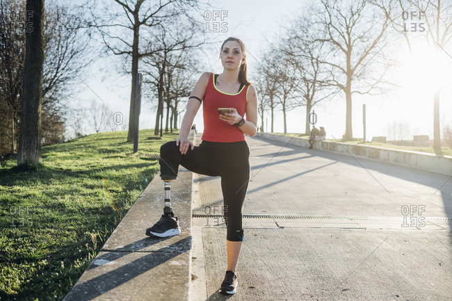 Sporty young woman with leg prosthesis holding cell phone