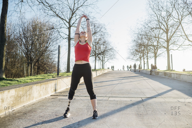 Sporty young woman with leg prosthesis raising her arms