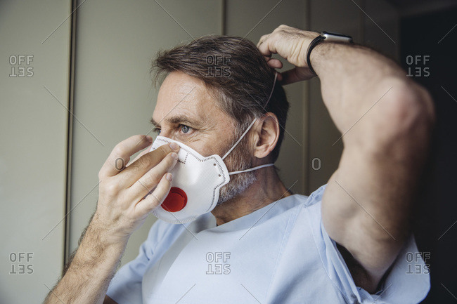 Male health worker putting on FFP3 mask