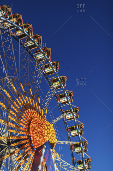 January 21, 2020: Germany- Bavaria- Munich- Low angle view of Ferris wheel glowing against clear sky at dusk