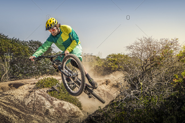 Young man jumping with mountain bike on dusty single trail- Fort Ord National Monument Park- Monterey- California- USA