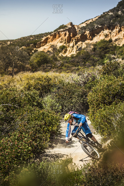 Mountain biker riding down dusty single trail- Fort Ord National Monument Park- Monterey- California- USA