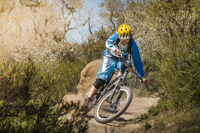 Man riding mountain bike on dusty trail- Fort Ord National Monument Park- Monterey- California- USA