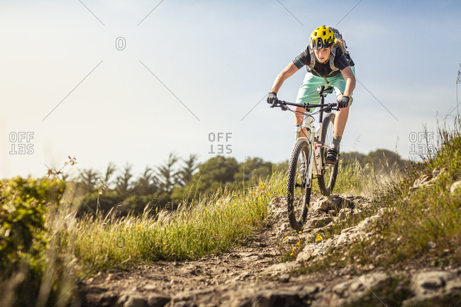 Woman on mountain bike riding down trail in front of blue sky- Santa Cruz- California- USA