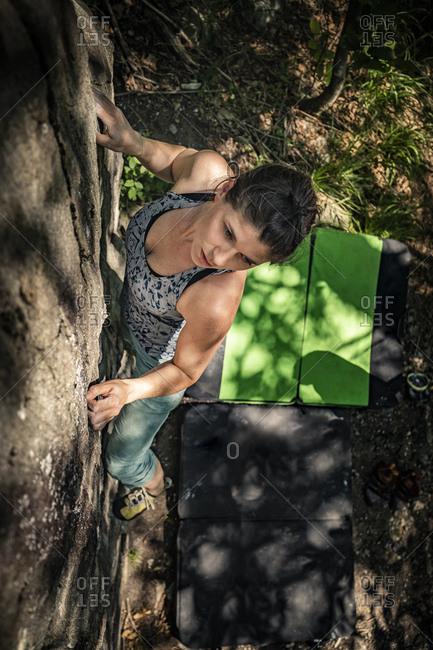 Female climber bouldering on rock- Averno- Ticino- Switzerland