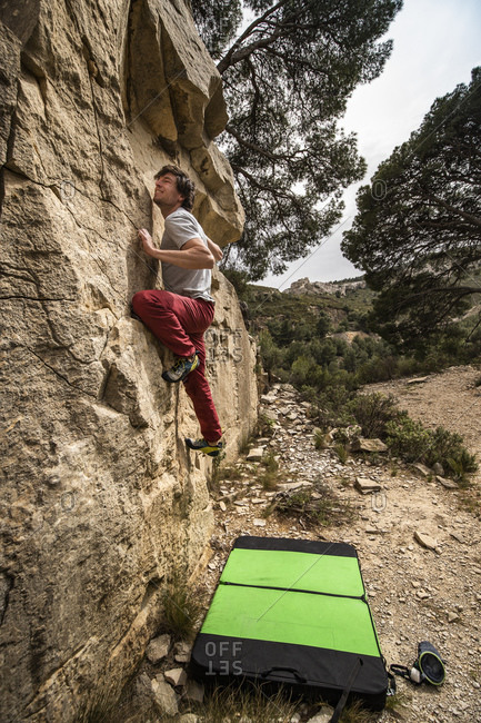 Climber bouldering on rock in quarry with crash pad on the ground- La Ciotat- Bouches-du-Rhone- France