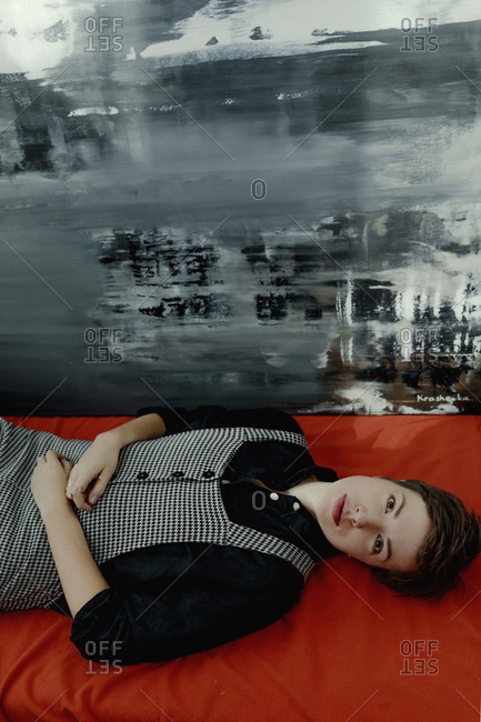 Portrait of a short-haired woman lying down beside painting