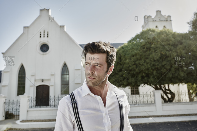 Portrait of man in old-fashioned clothes at a church in the countryside