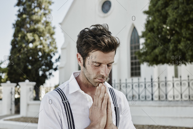 Portrait of man in old-fashioned clothes in the countryside praying at a church