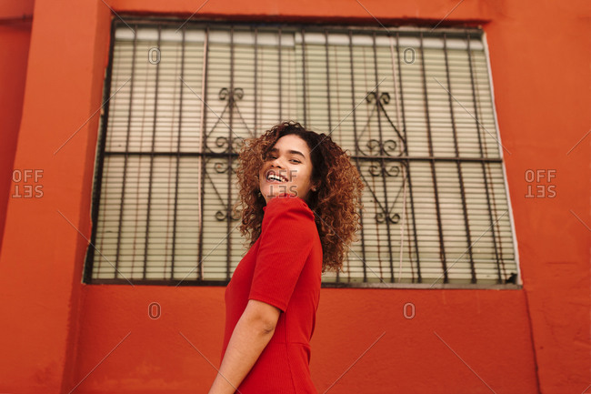 Portrait of happy woman with red dress- dancing in front of a red wall