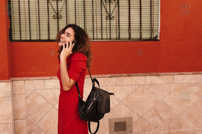 Portrait of happy woman with red dress- using smartphone