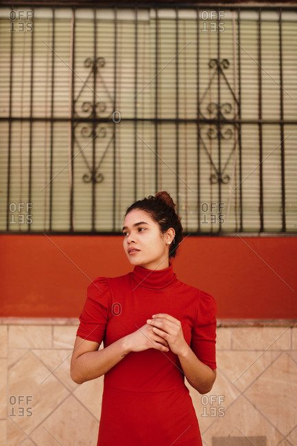 Portrait of melancholic woman with red dress looking sideways