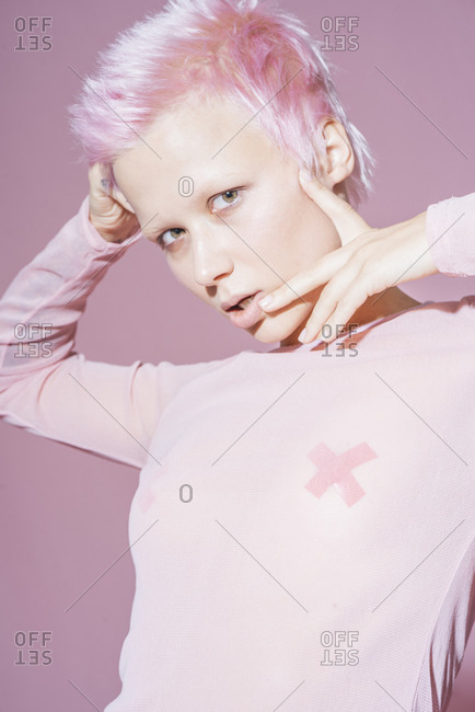 Portrait of young woman with short pink hair wearing pink top in front of pink background