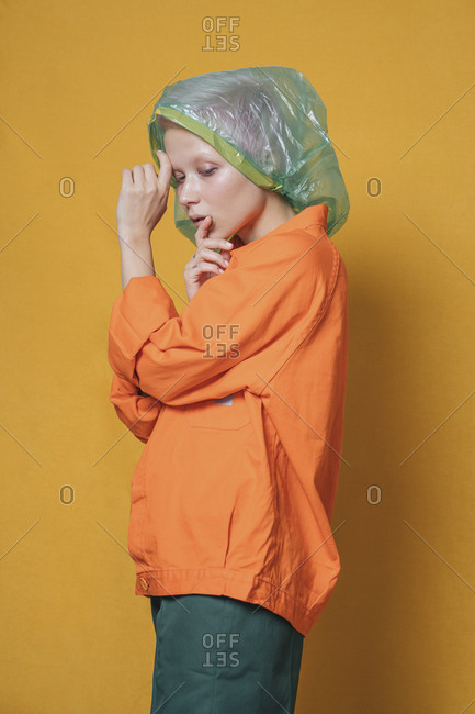 Portrait of young woman with plastic bag on her head wearing orange jacket in front of yellow background