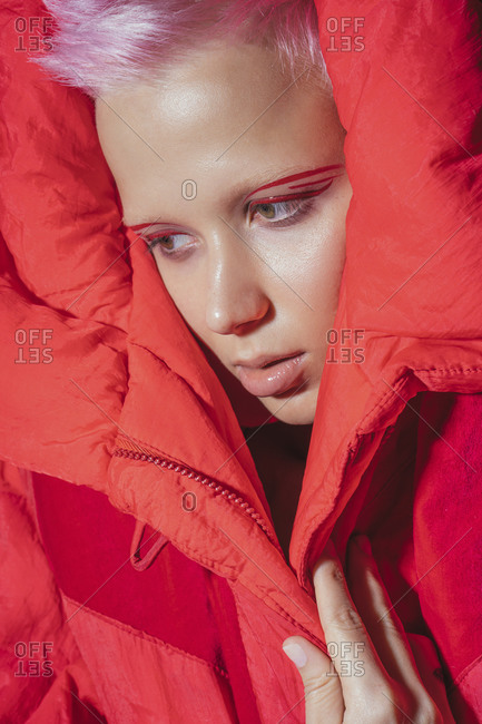 Portrait of young woman with short pink hair wearing red jacket in front of red background