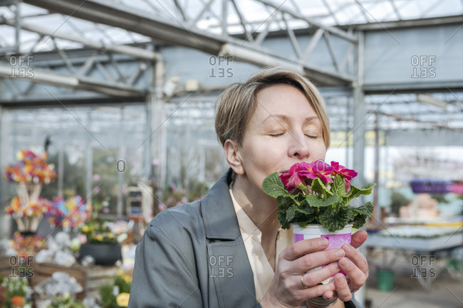 Woman with closed eyes sniffing pink flowers in flower shop