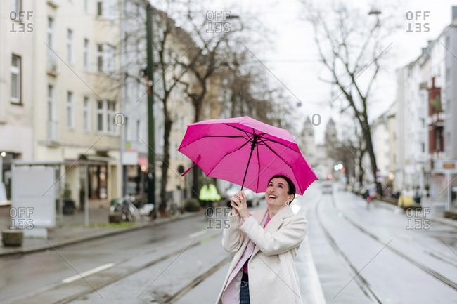 Smiling woman with pink umbrella walking on street