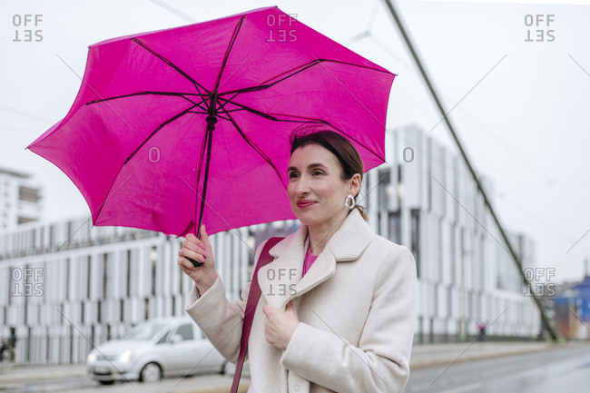 Smiling woman with pink umbrella walking in the city