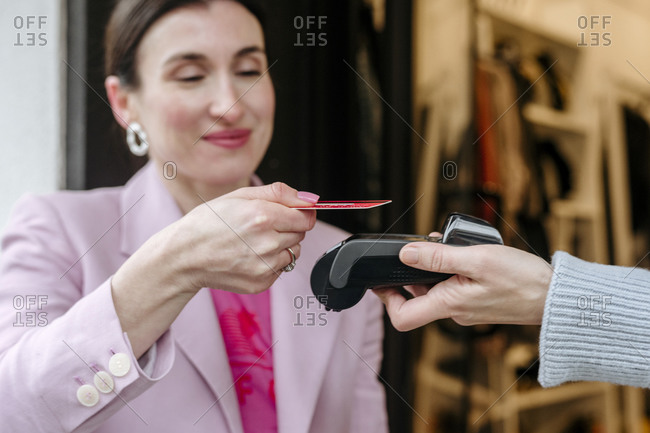 Smiling woman in pink jacket paying with her credit card