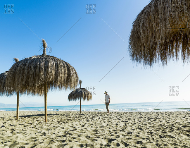 Man walking on the beach sand between umbrellas in Alamos Beach,