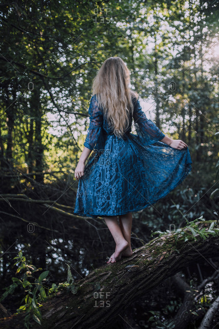 Girl in a blue dress stands on a tree fallen across a pond