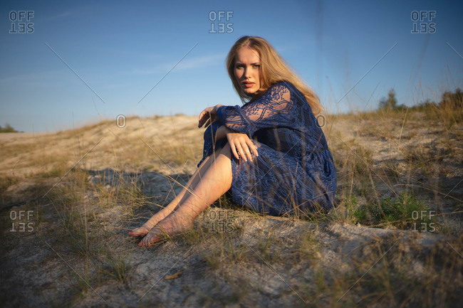 Woman sitting on a sand hill stares intently