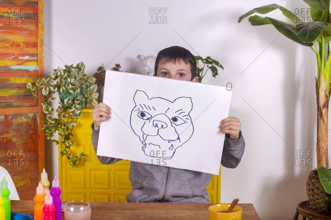 Boy showing his artwork at home.