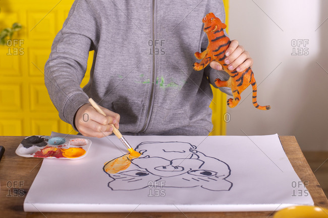 Boy with brush painting a tiger