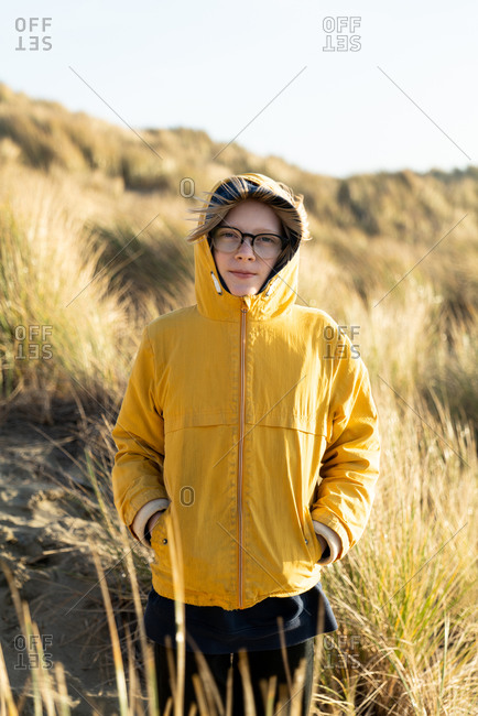 Tween standing in dunes covered in beach grass on the California coast