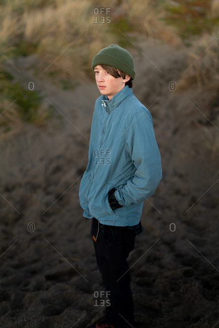 Teenage boy standing at the base of a dune on the coast at twilight