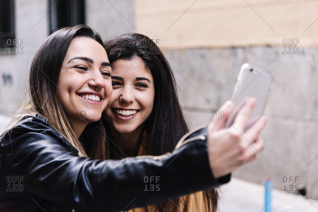 Beautiful Lesbian Couple Taking A Self Portrait At The Street. LGBT.