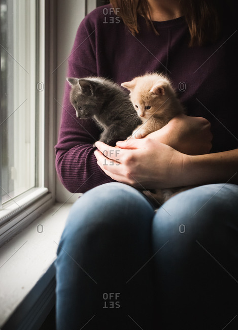 Woman holding two adorable kittens in her arms next to a window.