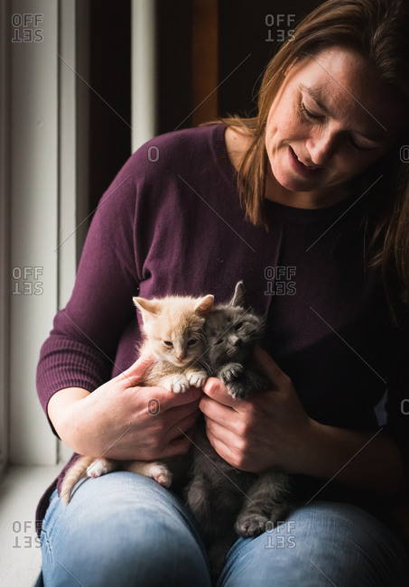 Woman looking at two adorable kittens that she is holding in her lap.