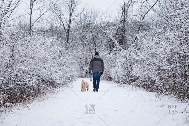 Man walking a dog on snowy trail through the woods on a winter day.