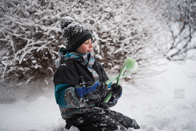 Young boy making snowball with snowball making toy on winter day.