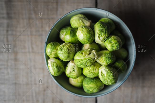 Overhead view of bowl of Brussels sprouts on wooden background.