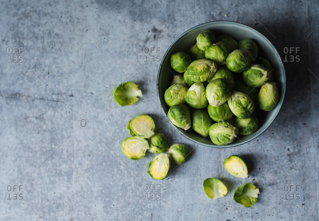 Overhead view of bowl of Brussels sprouts on cement counter.