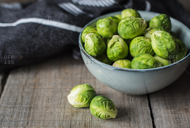Bowl of Brussels sprouts and napkin on a rustic wooden table.