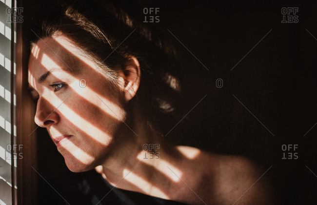 Portrait of woman looking out window with shadows across her face.