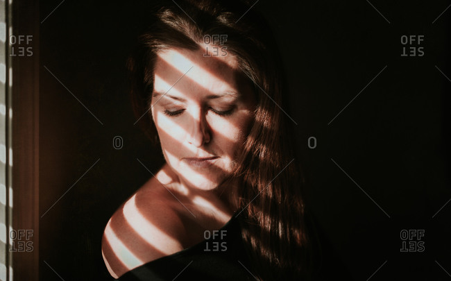 Portrait of woman beside a window with shadows across her face.