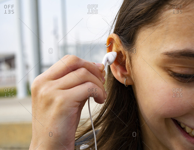 Woman putting a white headset on her ear.