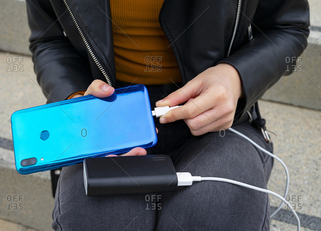 Woman connecting the mobile to a powerbank.