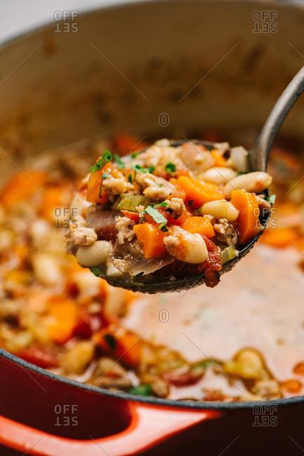 Spoon presentation detail of Italian sausage and white bean soup